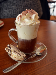 Delicious Viennese coffee in glass cup with whipped cream