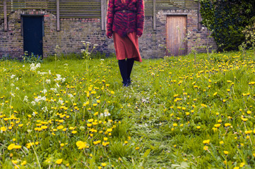 Woman walking in meadow with doors in the background