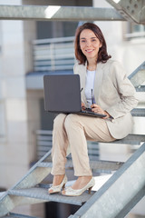 Smiling young businesswoman working on laptop