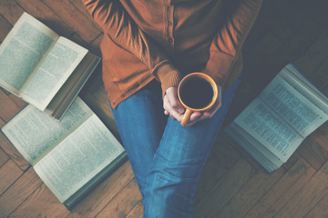 girl having a break with cup of fresh coffee after reading books