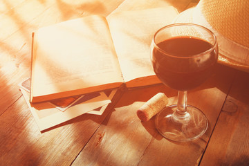 red wine glass and open book on wooden table at sunset burst