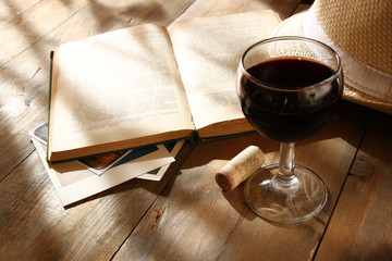 red wine glass and old open book on wooden table at sunset