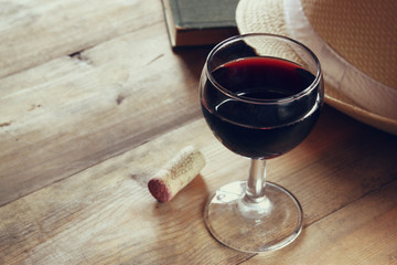 red wine glass and old book on wooden table at sunset burst