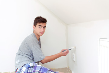 teenager painting wall to white at home