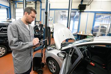 Gutachter prüft Fahrzeug in Autowerkstatt - TÜV
