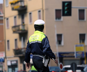 Italian policeman in uniform while blocking traffic with the Red