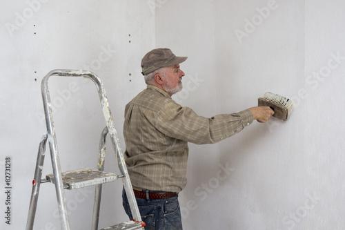 Tapezieren, Handwerker bestreicht die Wand mit Kleister\