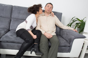 A couple on sofa relaxing together at home