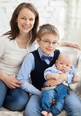 Happy mother with her children having fun in living room