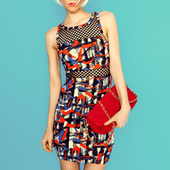 lady in fashionable dress bright prints.and accessories clutch.