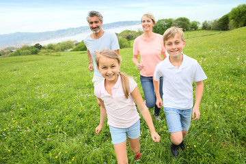 Family of four running in countryside