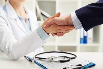 Woman doctor shaking hand with businessman in the office