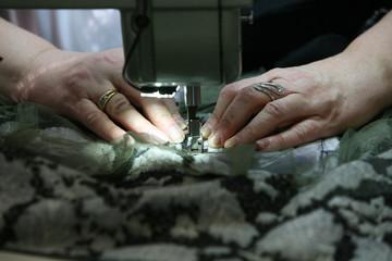 Mani che cuciscono un tessuto