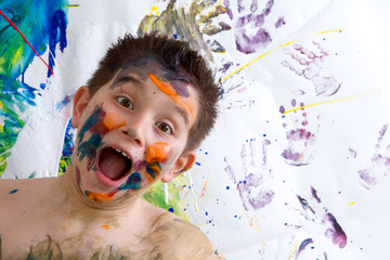 Excited happy little boy doing finger painting