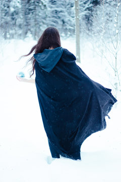 Witch in black cloak with magiс ball