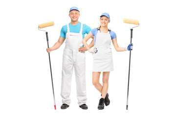 Male and female house painters holding paint rollers