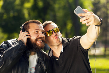 Two friends taking a selfie photo with mobile smart phone
