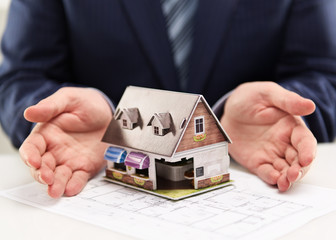 Male house agent showing family residence model to customers.