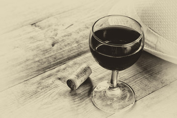 red wine glass and old book on wooden table. vintage filtered