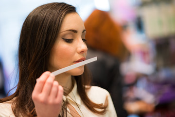 Fototapeta Woman smelling a perfume in a shop