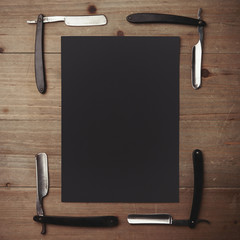 Straight razor and black picture frame on wood desk