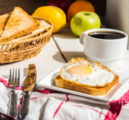 crispy toast with a fried egg and a cup of coffee, fruit, Englis