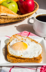 crispy toast with a fried egg and a cup of coffee, fruit, breakf
