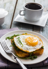 crispy toast with a fried egg and fresh arugula, a cup of coffee