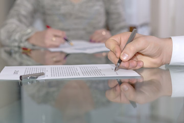 Male hand signing formal paper