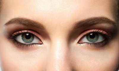 female blue eye with makeup with brown eyebrows and black lashes