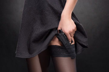 girl hand with a gun on a dark background in stockings
