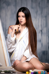 beautiful girl draws picture in the studio smeared with paint