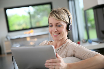 Middle-aged woman connected on tablet and wearing headset