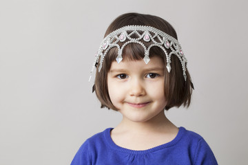 concept of spoilt child with tiara on young smiling girl's head