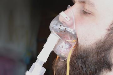 bearded man with an asthma inhaler to breathe health
