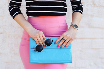 Wall Mural - Fashion woman in pink skirt stylish with blue clutch in hand