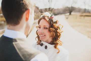 happy bride and happy groom having walk in park
