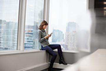 A woman sitting along, using a smart phone.