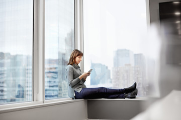 A woman holding a smart phone, sitting on a window ledge.