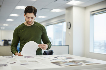 A man in an office checking proofs of printed pages.