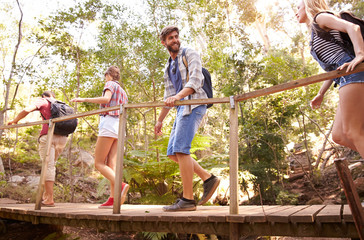 Group Of Friends On Walk Crossing Wooden Bridge In Forest