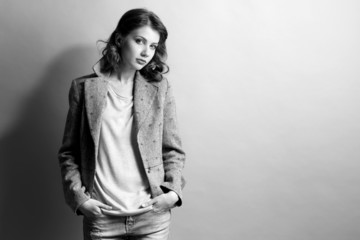 Portrait of beautiful model in jeans and jacket, in shades of grey