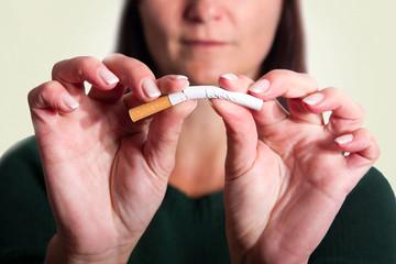 Frau biegt eine Zigarette , farbiger Hintergrund