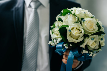Groom holding bouquet. Concept image - young man waiting woman
