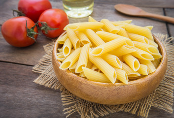Raw penne pasta in wooden bowl