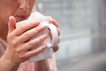 woman blowing hot tea
