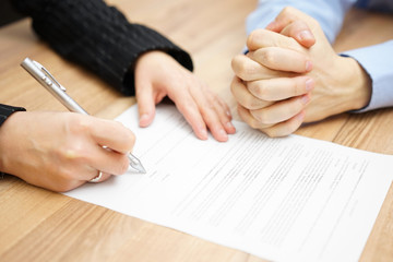 Man  with his hands clasped is waiting woman to sign the contrac