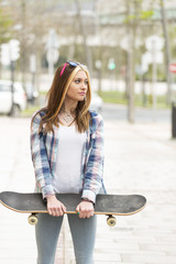 Beautiful casual young woman with skateboard, urban lifestyle.