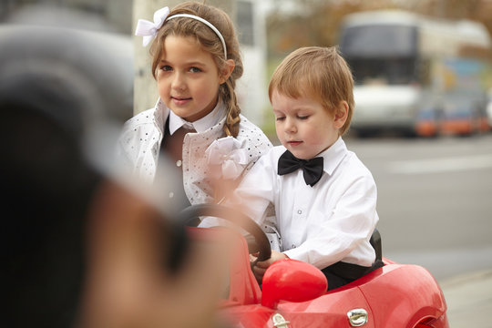 girl and boy in a white shirt in a red toy car in the street