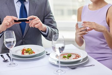 close up of couple with smartphones at restaurant